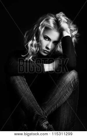 Black-and-white portrait of a calm, sad beautiful young woman looking at camera. Emotions. Beauty, fashion.