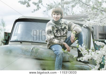 Relaxing Teenager Wearing Woolly Hand-knitted Reindeer Sweater Sitting Outdoors On Old Truck Body At