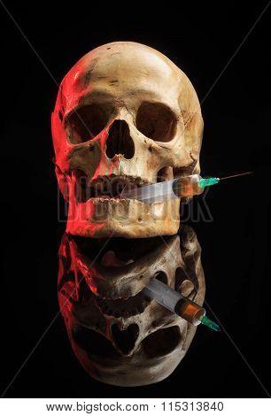Skull and syringe of yellowish liquid. concept drugs