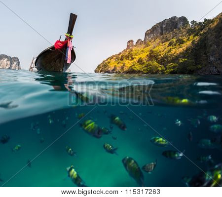 Split shot with fish underwater and long tail boat on the surface. Focus on the boat only