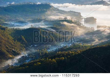 Morning fog in the valley with lake and villages. View from the mountain of Adam's Peak, Sri Lanka