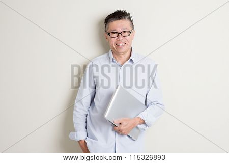 Portrait of modern mature 50s Asian man in casual business holding laptop computer and smiling, standing over plain background with shadow. Chinese senior male people.