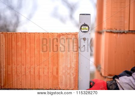 Construction Worker Measuring With Professional Level The Bricks On Walls