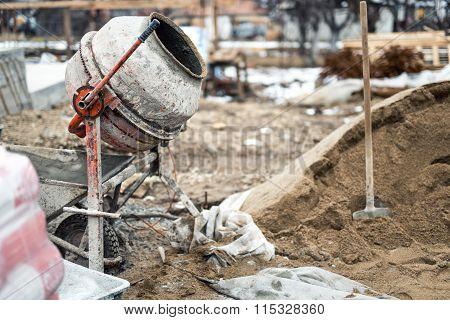Industrial Cement Mixer Machine At House Construction Site. Concrete Mixer, Sand And Tools