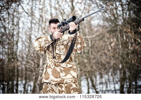 Sniper With Weapon Ready For Combat Or Hunting In The Forest On A Winter Day