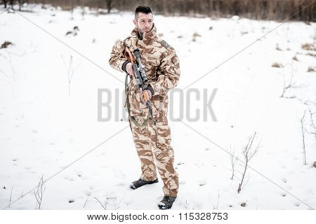 Army Ranger With Automatic Machine Gun Performing Patrol In A Snowy Forest