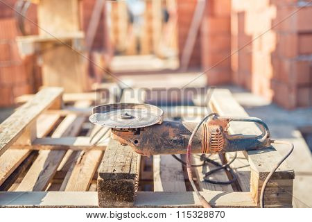 Tools And Accesories On Construction Site - Angle Cutter, Electric Grinder And Wooden Blocks
