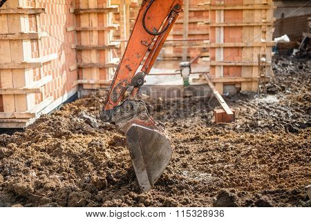 Close Up Of Excavator Scoop Digging Earth At Construction Site