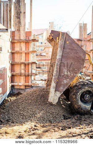 Dumper Truck Unloading Construction Gravel, Granite And Crushed Stones At Building Foundation