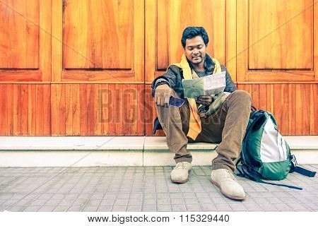 Young Indian Guy Looking City Map Holding Mobile Phone - Asian Model Male Next To Old Wooden Door