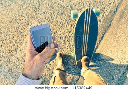 Man Holding Mobile Phone Closeup Top View - Young Skateborder On The Road Addicted To Smartphone