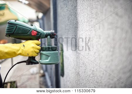 Worker Painting Wall With Grey Paint Using A Professional Spray Gun. Man Painting Wall