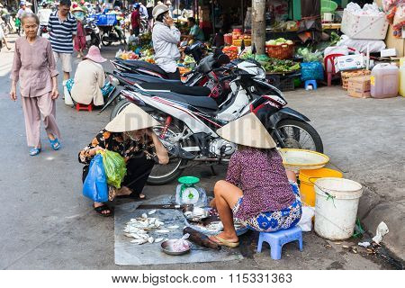 Vietnamese woman in traditional conical hat is selling fish at the wet market
