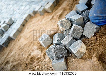 Construction Worker Placing Cobblestone, Granite Stone On Pavement