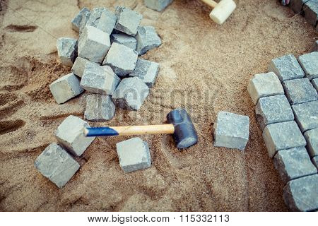 Stone Pavement Blocks, On Sand, With Tools And Construction Details. Laying The Pavement Cobblestone