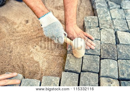 Construction Worker Installing Stone Blocks, Creating Pavement On Road, Sidewalk Or Path
