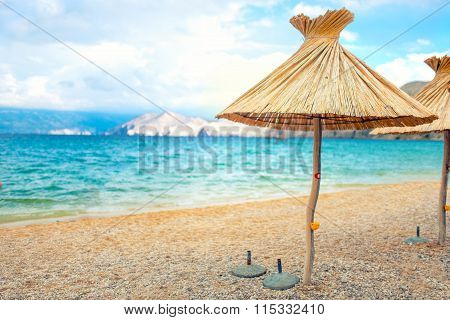 Beach Straw Umbrella Lounger Chair With Sand And Clear Water. Sea Mediteraneean Coastline Landscape