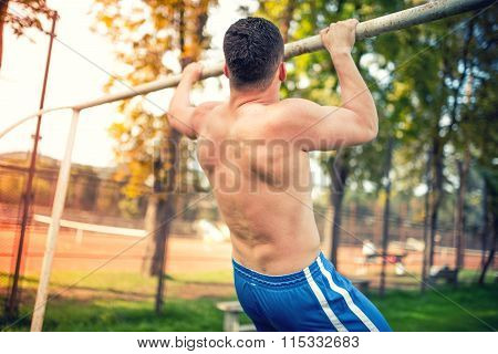 Muscular Athletic Man Working Out In Park, Training And Doing Pull Ups. Vintage Dual Color Effect On