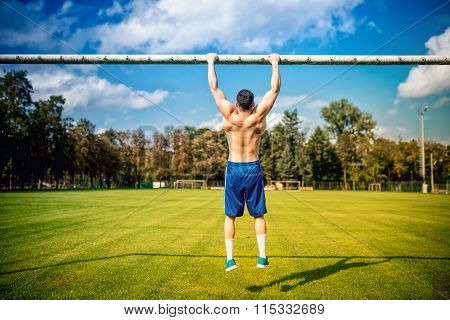 Atheltic Built Man Doing Chinups And Core Training In Park. Fitness Football Player Training On Gras