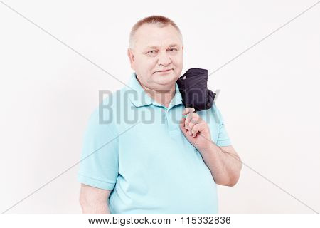 Mature cheerful man wearing blue shirt holding jacket over his shoulder and smiling against white wall - casual dress code concept