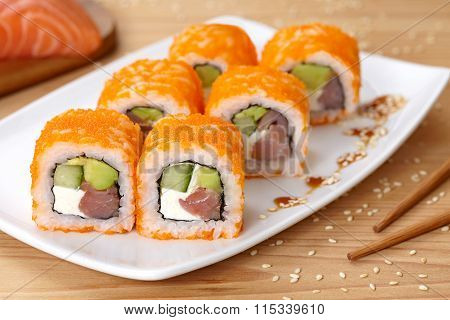 Philadelphia sushi roll with smoked salmon, avocado, cream cheese, cucumber and tobiko caviar.