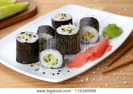 Maki sushi roll with cucumber, wasabi, ginger and nori seaweed.