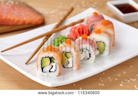Rainbow dragon sushi roll with salmon, avocado, soft cheese, cucumber and tobiko caviar