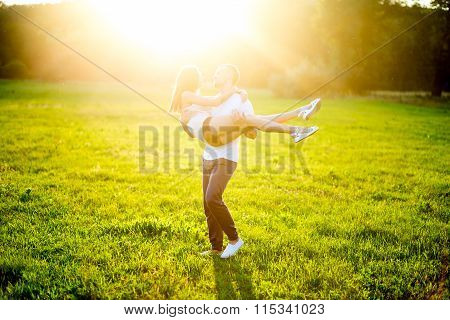 Happy Young Couple In Nature Fun. Guy Holds Girl On Hands