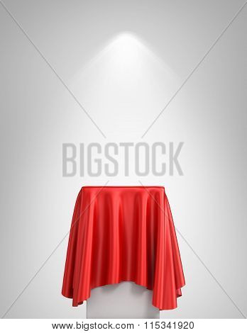 Presentation Pedestal Covered With A Red Silk Cloth In Front Of A White Wall Illuminated By A Spot L