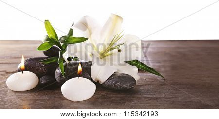 Spa still life with beautiful flower and candlelight on wooden table, closeup