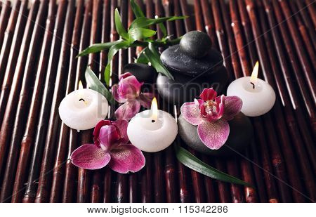 Spa still life with beautiful flower and candlelight on bamboo sticks background