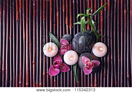 Spa still life with beautiful flower and candlelight on bamboo sticks, top view