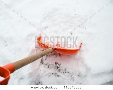 Snow removal. Orange Shovel in snow
