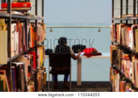 Blurred Books And Student Studying In A Library