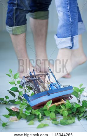 Small Toy Ship On The Background Of Boyfriend And Girlfriend Feet.
