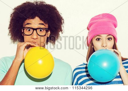 Funky Young Couple Inflating Balloons While Standing Against White Background