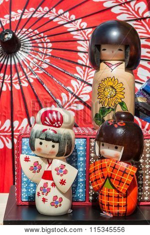 Traditional Japanese Wooden Kokeshi Dolls And Wagasa Umbrella In Background
