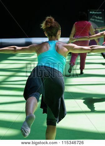 Young Woman Trying The Virabhadrasana Yoga Pose