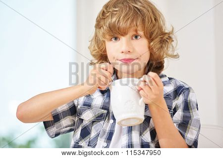 Happy boy eating and drinking from a cup of hot chocolate