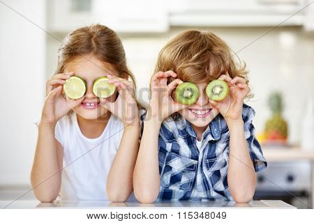 Two kids in kitchen hiding their eyes behind fruits