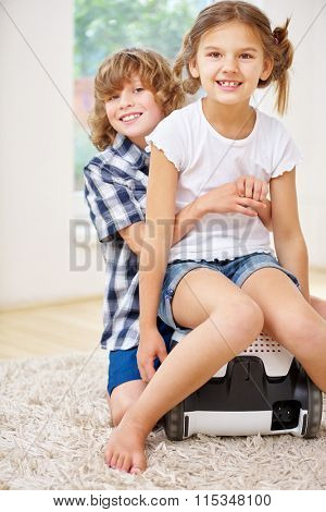 Happy siblings sitting on vacuum cleaner and smiling at home