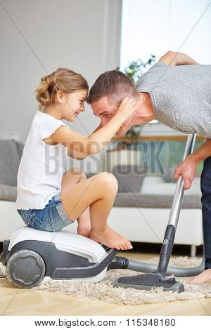 Father and daughter having fun with vacuum cleaner while cleaning at home