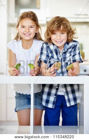 Two happy children holding kiwi halves in the kitchen