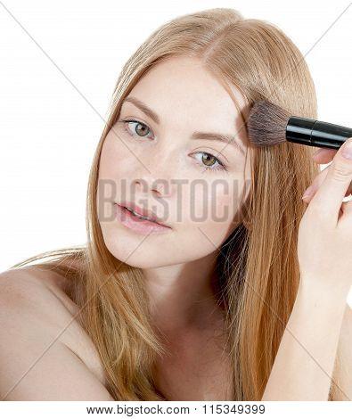 Young beautiful girl applying powder by brush