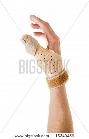 Hand Wearing Brace Over Thumb In White Studio