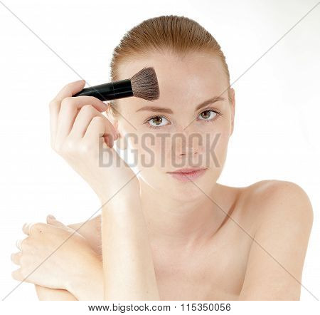 Young Beautiful Girl Applying Makeup By Brush On Her Face.