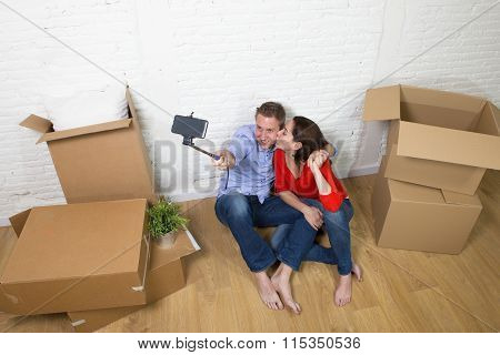 Young Happy Couple Sitting On Floor Celebrating Moving In New House Taking Selfie Photo