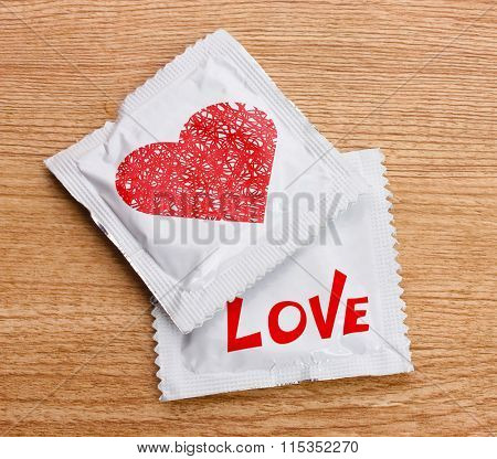 Condoms with heart on wooden table