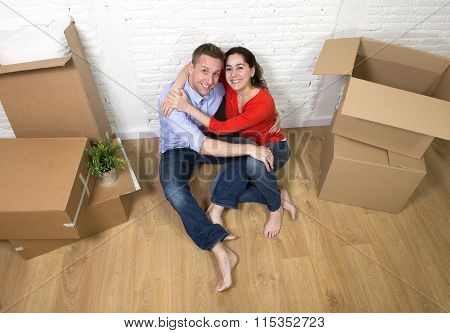 Young Happy Couple Sitting On Floor Celebrating Moving In A New House
