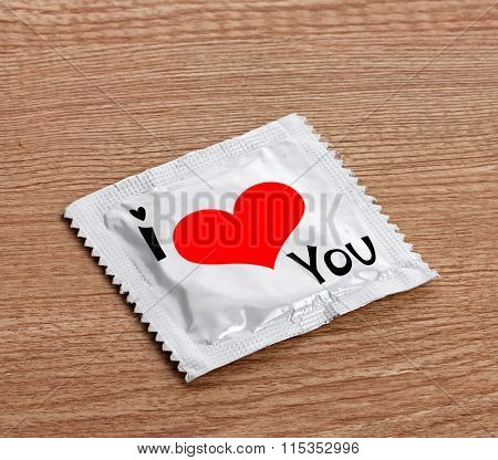 Condom with text I love you on wooden table